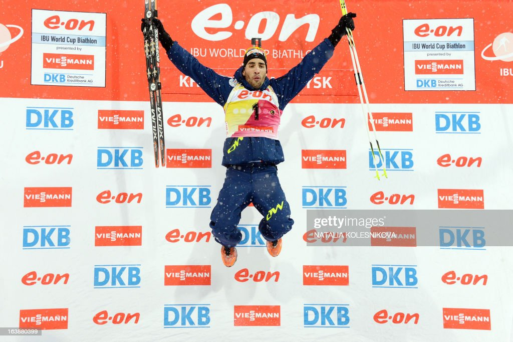 France's Martin Fourcade celebrates on the podium after winning the men's 15 km mass start event of the IBU Biathlon Word Cup in the Siberian city of Khanty-Mansiysk, on March 17, 2013. France's Martin Fourcade took the first place ahead of Austria's Dominik Landertinger and Norway's Emil Hegle Svendsen.