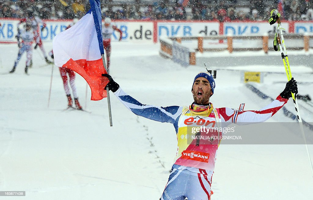 France's Martin Fourcade crosses the finish line in first place during the men's 15 km mass start event of the IBU Biathlon Word Cup in the Siberian city of Khanty-Mansiysk, on March 17, 2013. France's Martin Fourcade took the first place ahead of Austria's Dominik Landertinger and Norway's Emil Hegle Svendsen.