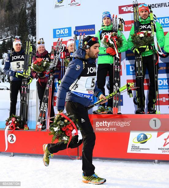 France's Martin Fourcade leaves a podium after the winners ceremony of the 2017 IBU World Championships Biathlon mixed relay race in Hochfilzen on...
