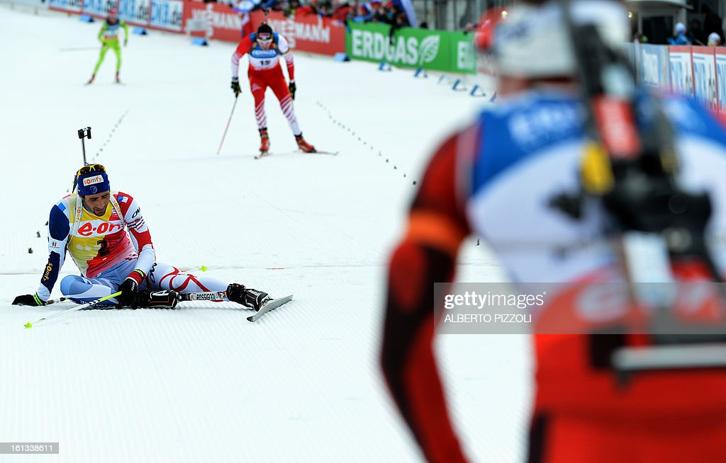 France's Martin Fourcade (L) reacts after falling in front of the finish line as the winner, Norway's Emil Hegle Svendsen looks at him during the pursuit men12,5 km as part of IBU Biathlon World Championships in Nove Mesto, Czech Republic, on February 10, 2013. Svendsen won ahead of France's Martin Fourcade and Russia's Anton Shipulin.