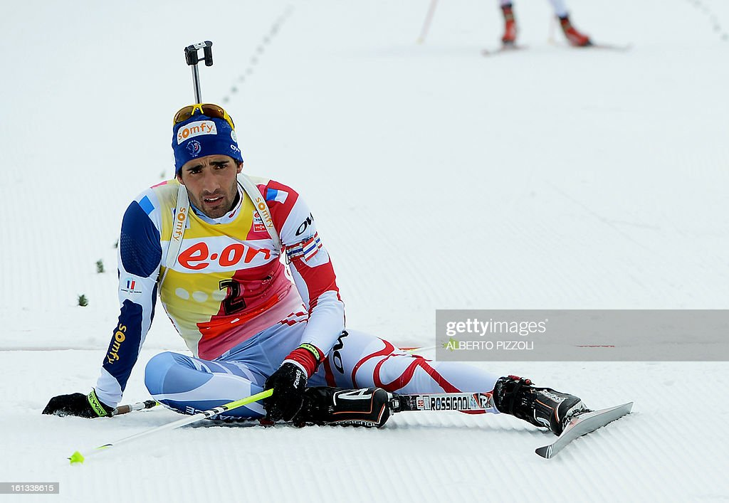 France's Martin Fourcade (L) reacts after falling in front of the finish line during the pursuit men12,5 km as part of IBU Biathlon World Championships in Nove Mesto, Czech Republic, on February 10, 2013.Norway's Emil Hegle Svendsen won ahead of France's Martin Fourcade and Russia's Anton Shipulin. AFP PHOTO / ALBERTO PIZZOLI