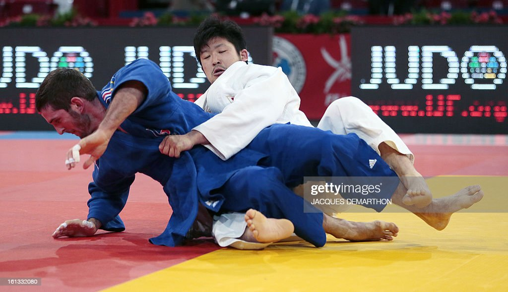 France's Maxime Clement (blue) fights against Japan's Kobayashi Daisuke (white) on February 10, 2013 in Paris, during the eliminatories of the Men - 100kg of the Paris Judo Grand Slam tournament.