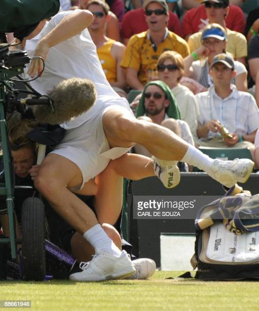 France's Michael Llodra collides with a ball girl during play against Germany's Tommy Haas during their second round match in the 2009 Wimbledon...