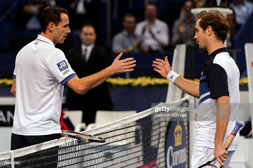 France's Michael Llodra (L) shakes hands with his compatriot Richard Gasquet after he won 6-4, 6-2 their match at the Swiss Indoors ATP tennis tournament on October 23, 2013 in Basel.