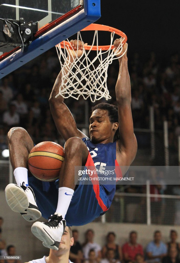 France's Mickael Gelabale hangs off the rim during a friendly basketball match between France and Serbia on August 15, 2013 in Antibes, southeastern France as part of the preparation for the 2013 EuroBasket in Slovenia.