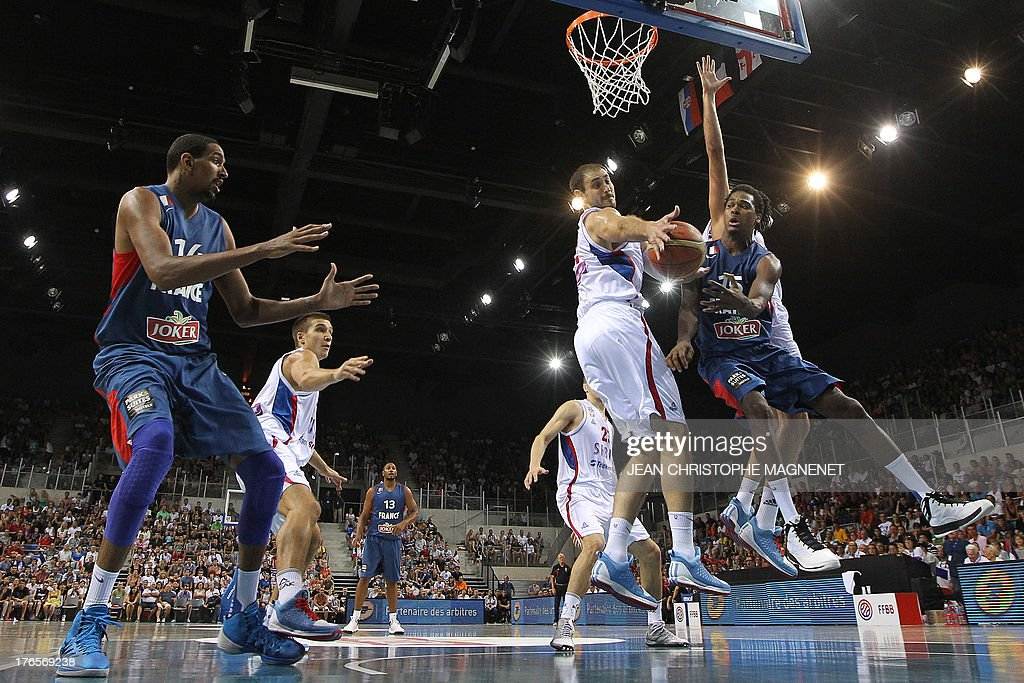 France's Mickael Gelabale (R) vies with Serbia's Nenad Krstic (C) during a friendly basketball match between France and Serbia on August 15, 2013 in Antibes, southeastern France as part of the preparation for the 2013 EuroBasket in Slovenia.