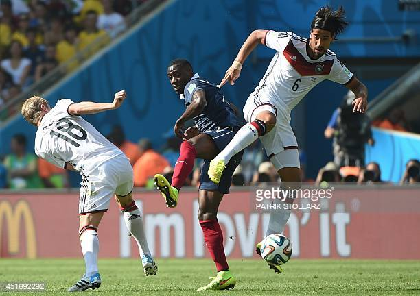 France's midfielder Blaise Matuidi tackles Germany's midfielder Sami Khedira and Germany's midfielder Toni Kroos during the quarterfinal football...