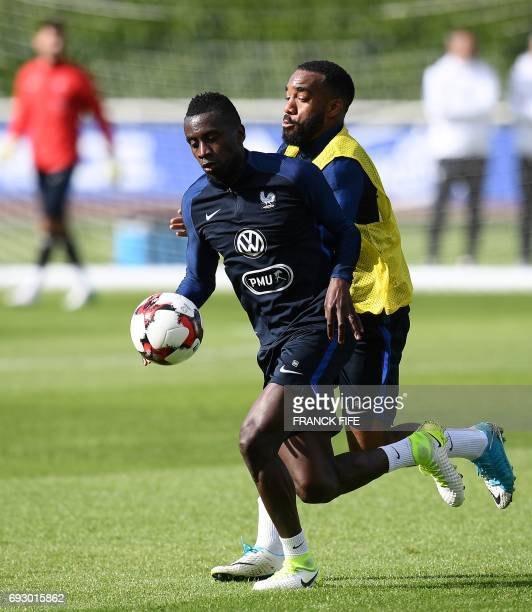 France's midfielder Blaise Matuidi vies with France's forward Alexandre Lacazette during a training session in Clairefontaine en Yvelines on June 6...