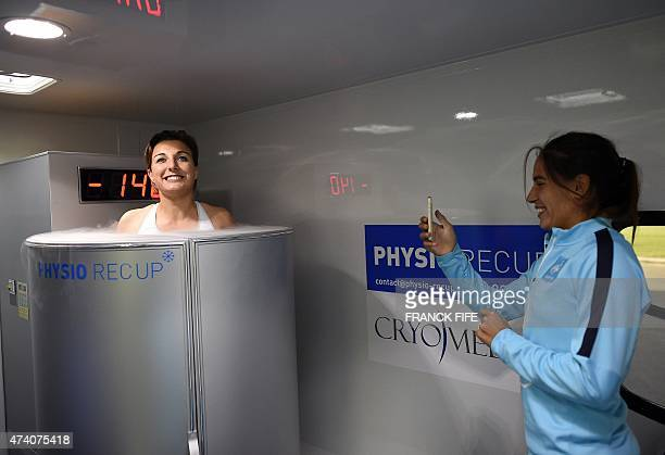 France's midfielder Claire Lavogez stands in a medical device used for cryotherapy next to France's defender Amel Majri at the French national...