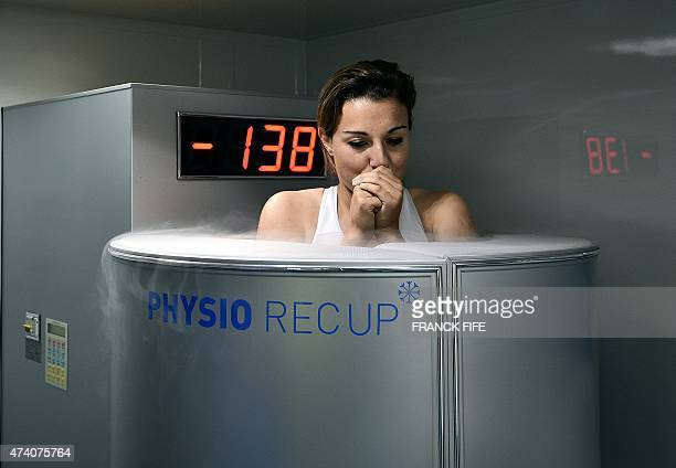 France's midfielder Claire Lavogez stands in a medical device used for cryotherapy at at the French national football team training base in...