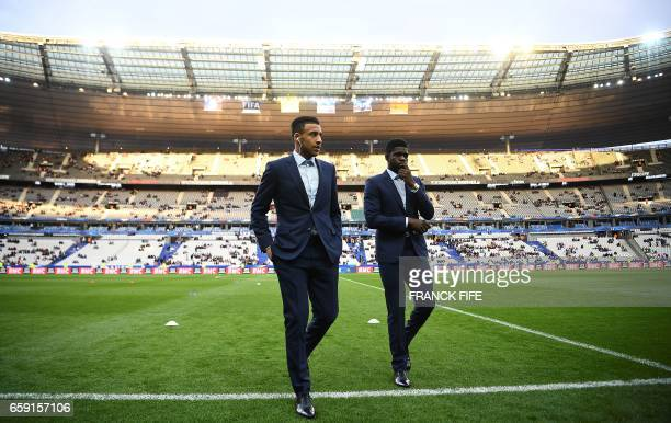 France's midfielder Corentin Tolisso and France's defender Samuel Umtiti walk on the pitc ahead of the friendly football match France vs Spain on...