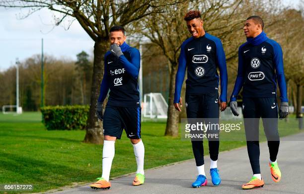 France's midfielder Corentin Tolisso defender Presnel Kimpembe and forward Kylian Mbappe arrive for a training session in Clairefontaine near Paris...