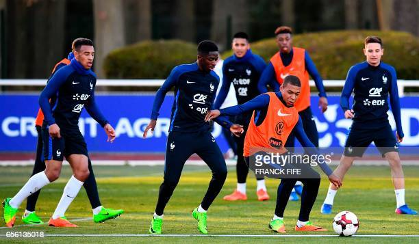 France's midfielder Corentin Tolisso forward Ousmane Dembele and forward Kylian Mbappe take part in a training session in Clairefontaine near Paris...