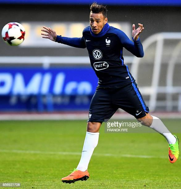 France's midfielder Corentin Tolisso heads the ball during a training session in Clairefontaine on March 23 near Paris as part of the team's...