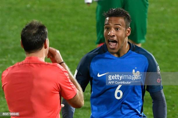 France's midfielder Corentin Tolisso speaks with referee Antonio Mateu Lahoz during the FIFA World Cup 2018 qualifying football match between...