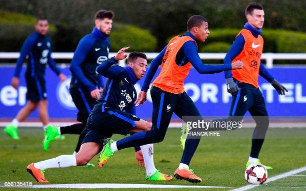 France's midfielder Corentin Tolisso vies with forward Kylian Mbappe during a training session in Clairefontaine near Paris on March 21 as part of...