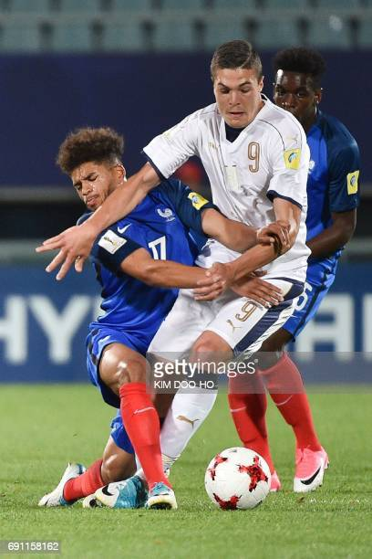 France's midfielder Denis Wil Poha fights for the ball with Italy's forward Andrea Favilli during their U20 World Cup round of 16 football match...