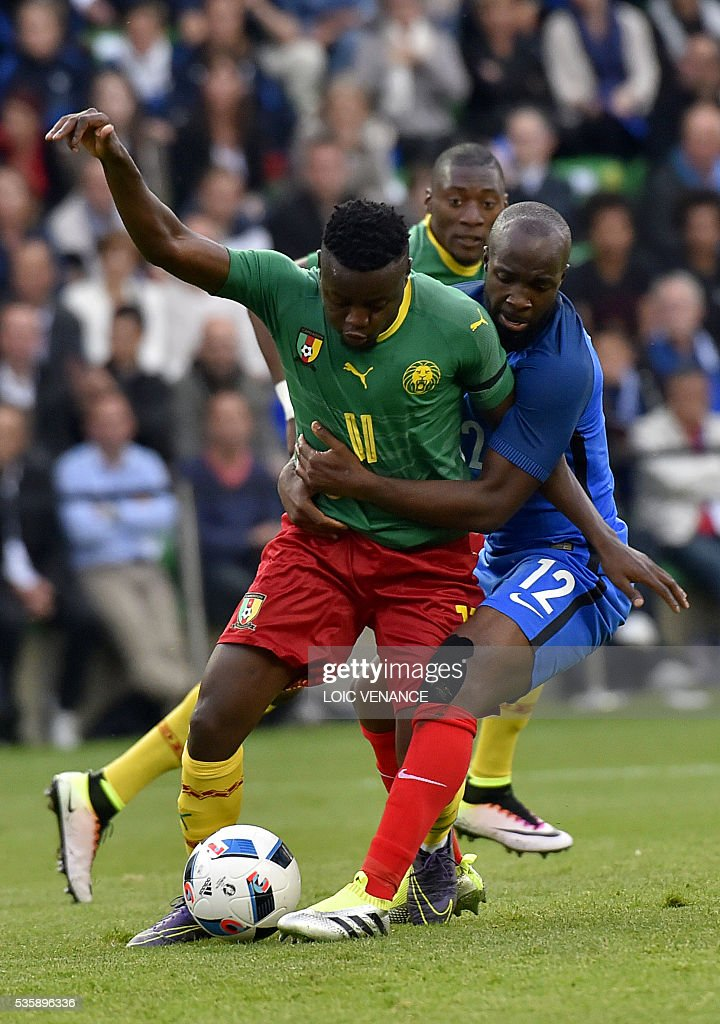 France's midfielder Lassana Diarra (rear R) fights for the ball with Cameroon's forward Edgar Salli (front L) during the International friendly football match between France and Cameroon at the Beaujoire stadium, in Nantes, western France, on May 30, 2016 as part of the French team's preparation for the upcoming Euro 2016 European football championships. / AFP / LOIC