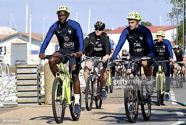 France's midfielder Moussa Sissoko and forward Hatem ben Arfa ride bicycle along the seafront following the team's arrival in Biarritz at the start...