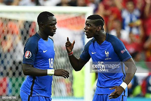 France's midfielder Moussa Sissoko and France's midfielder Paul Pogba react during the last minutes of the Euro 2016 final football match between...