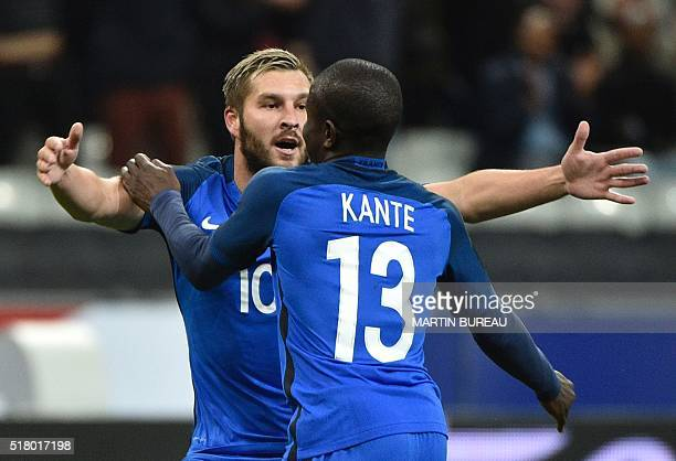 France's midfielder N'Golo Kante celebrates scoring the opening goal with France's forward AndrePierre Gignac during the international friendly...