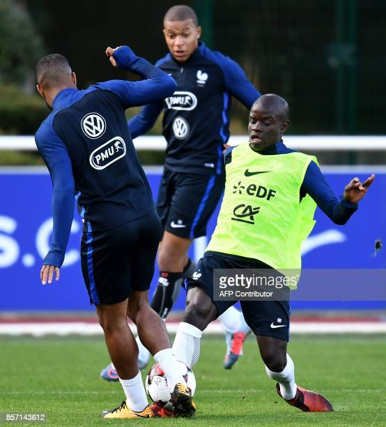 France's midfielder N'Golo Kante vies with France's forward Dimitri Payet during a training session in ClairefontaineenYvelines on October 3 in...