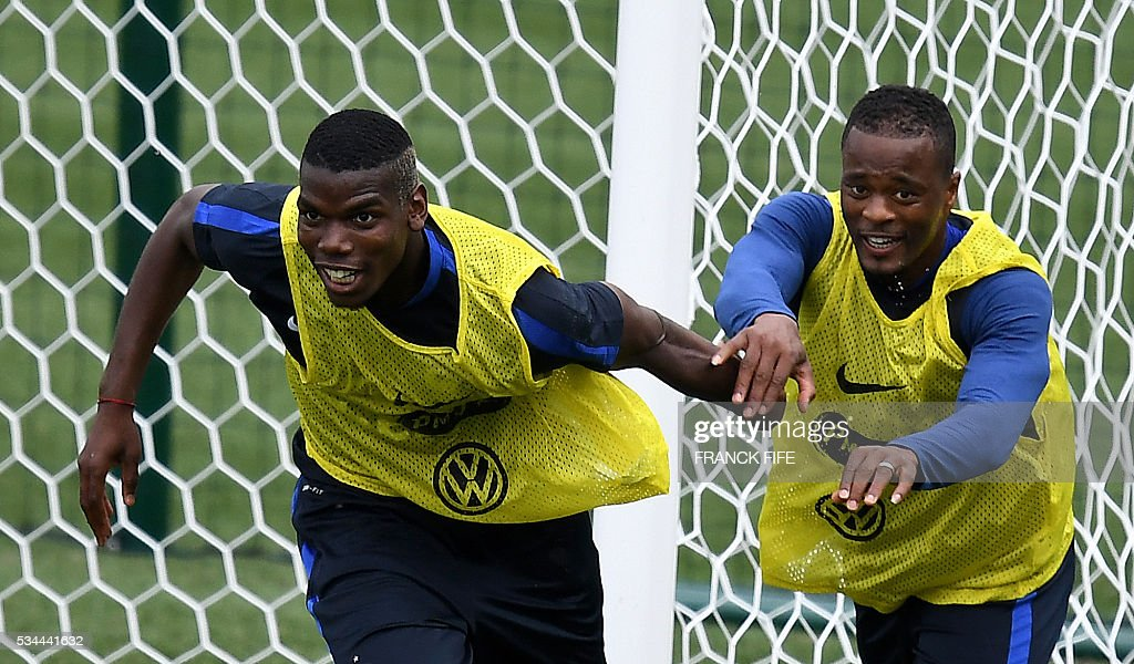 France's midfielder Paul Pogba (L) and France's defender Patrice Evra react during a training session in Clairefontaine en Yvelines on May 26, 2016, as part of the team's preparation for the upcoming Euro 2016 European football championships. / AFP / FRANCK