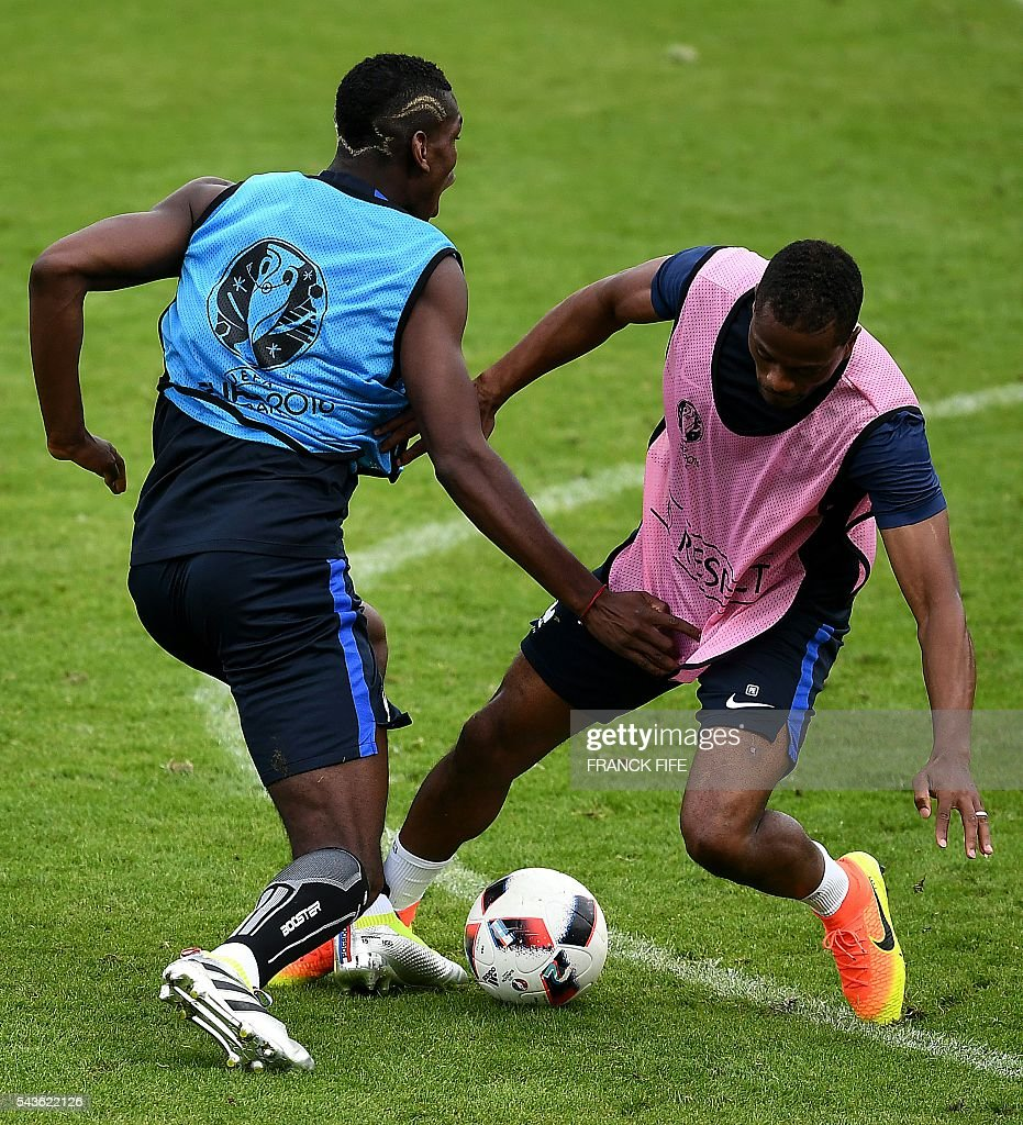 France's midfielder Paul Pogba (L) and France's defender Patrice Evra take part in a training session in Clairefontaine-en-Yvelines, southwest of Paris, on June 29, 2016, during the Euro 2016 football tournament. / AFP / FRANCK