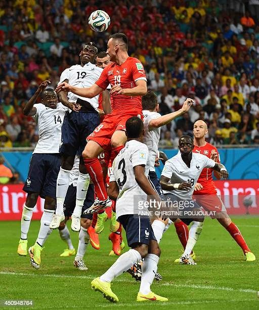 France's midfielder Paul Pogba and Switzerland's forward Josip Drmic jump for the ball during a Group E football match between Switzerland and France...