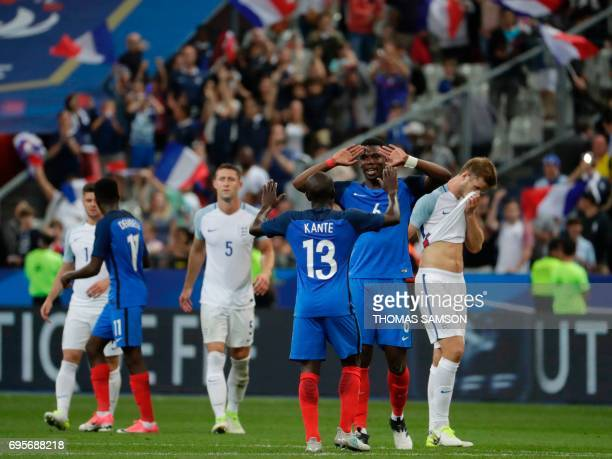 France's midfielder Paul Pogba and teammate defender N'golo Kante celebrate victory in the international friendly football match between France and...