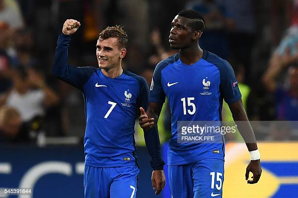 France's midfielder Paul Pogba celebrates with France's forward Antoine Griezmann who scored a penalty shot giving France the first goal of the match...