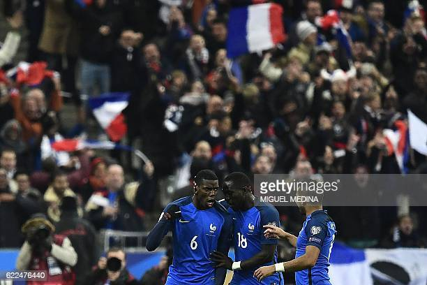 France's midfielder Paul Pogba celebrates with France's midfielder Dimitri Payet and France's midfielder Moussa Sissoko after scoring a goal during...