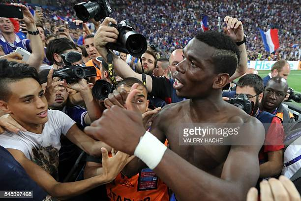 France's midfielder Paul Pogba celebrates with supporters after winning the Euro 2016 semifinal football match between Germany and France at the...