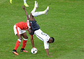 TOPSHOT France's midfielder Paul Pogba falls down as he vies with Switzerland's forward Breel Embolo during the Euro 2016 group A football match...