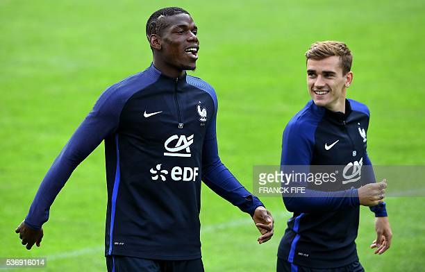 France's midfielder Paul Pogba jokes with France's forward Antoine Griezmann during a training session in Neustift im Stubaital on June 1 as part of...