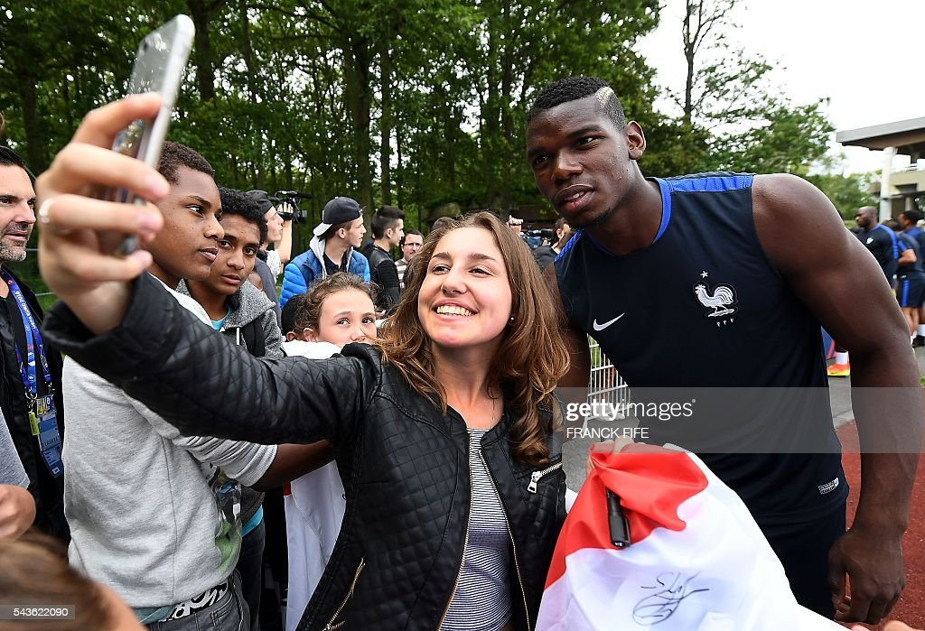 France's midfielder Paul Pogba (R) poses for a selfie with a fan before a training session in Clairefontaine-en-Yvelines, southwest of Paris, on June 29, 2016, during the Euro 2016 football tournament. / AFP / FRANCK