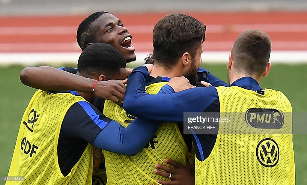 France's midfielder Paul Pogba (L) reacts with teammates during a training session in Clairefontaine en Yvelines on May 26, 2016, as part of the team's preparation for the upcoming Euro 2016 European football championships. / AFP / FRANCK