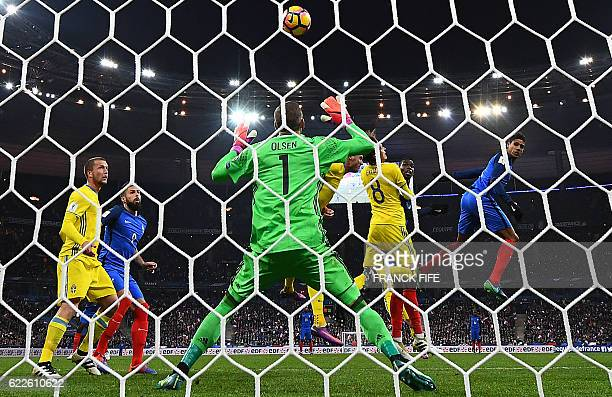 France's midfielder Paul Pogba scores a goal next to France's defender Raphael Varane in front of Sweden's goalkeeper Robin Olsen during the 2018...