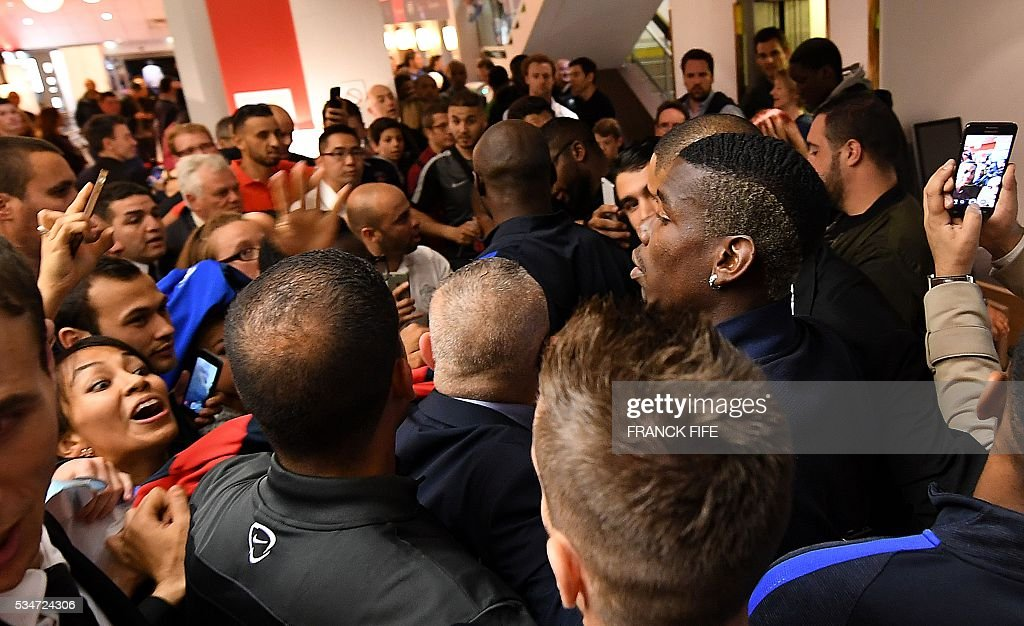 France's midfielder Paul Pogba (C-R) signs autographs at Vincennes racetrack, on May 27, 2016 in Vincennes, on the sideline of the team's preparation for the friendly football match France vs Cameroun as part of the team's preparation for the upcoming Euro 2016 European football championships. / AFP / FRANCK