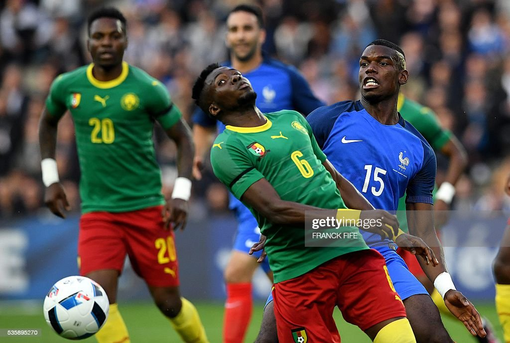 France's midfielder Paul Pogba (R) vies for the ball with Cameroon's defender Ambroise Oyongo Bitolo during the friendly football match between France and Cameroon, at the Beaujoire Stadium in Nantes, western France, on May 30, 2016. / AFP / FRANCK