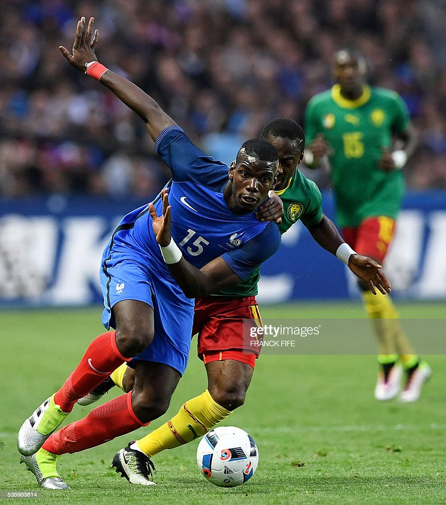 France's midfielder Paul Pogba (L) vies with Cameroon's midfielder Eyong Enoh Tarkang during the friendly football match between France and Cameroon, at the Beaujoire Stadium in Nantes, western France, on May 30, 2016. / AFP / FRANCK