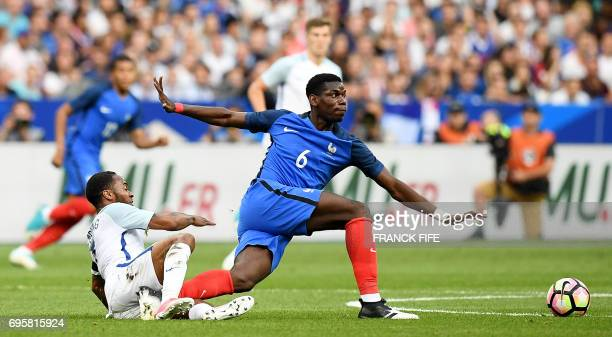 TOPSHOT France's midfielder Paul Pogba vies with England's midfielder Raheem Sterling during the friendly football match France vs England on June 13...