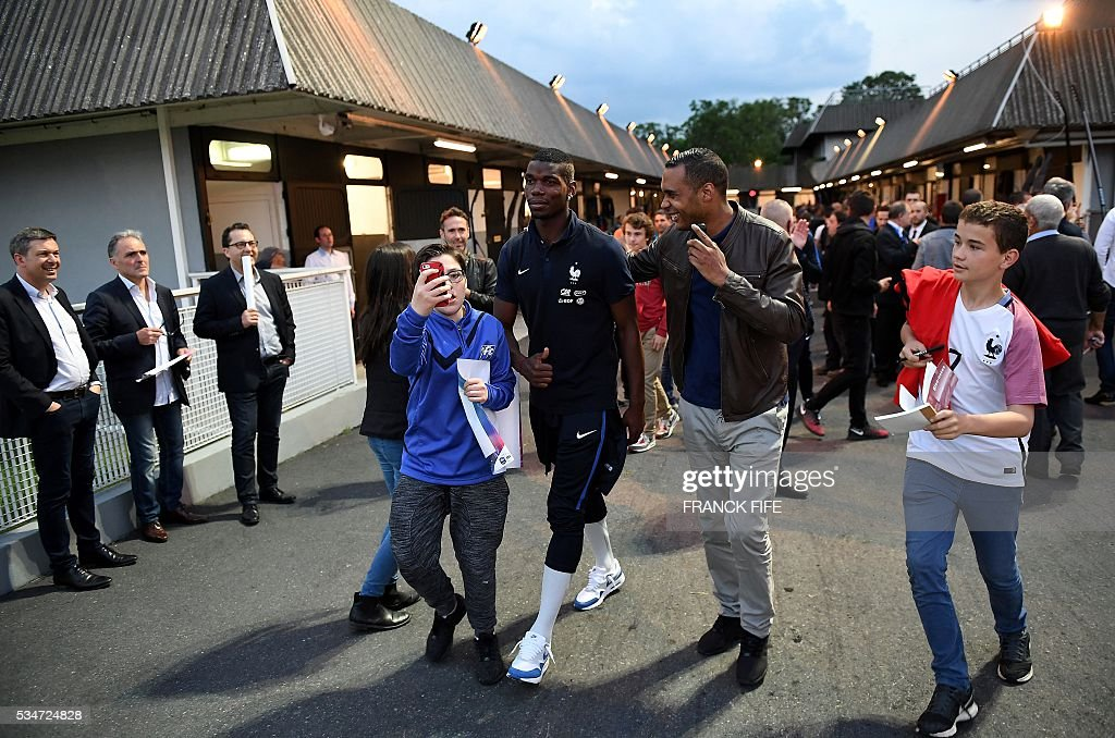 France's midfielder Paul Pogba (C) walks at Vincennes racetrack, on May 27, 2016 in Vincennes, on the sideline of the team's preparation for the friendly football match France vs Cameroun as part of the team's preparation for the upcoming Euro 2016 European football championships. / AFP / FRANCK