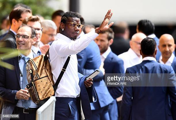 France's midfielder Paul Pogba waves at supporters as France's national football team players leave their hotel on their way to the Elysee Palace in...