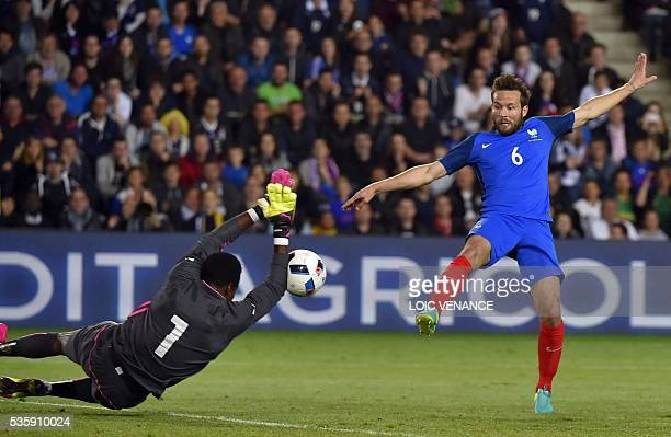 France's midfielder Yohan Cabaye tries to score as Cameroon's goalkeeper Fabrice Ondoa attempts to block the ball during the International friendly...