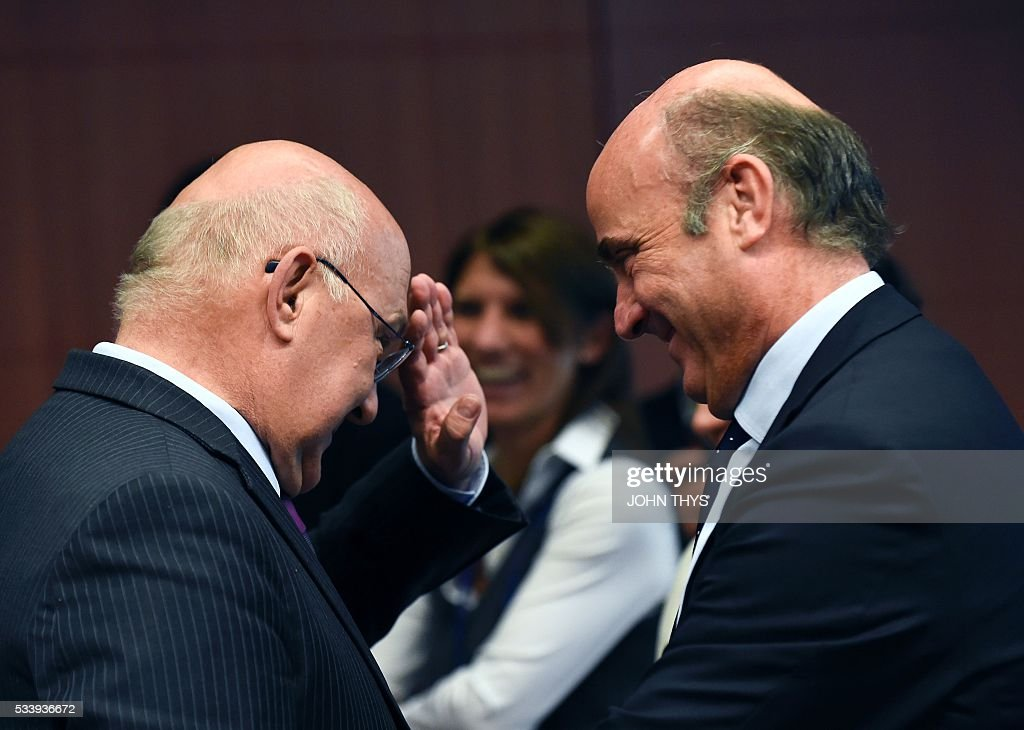 France's Minister of Finance and Public Accounts Michel Sapin (L) talks with Spanish Economy Minister Cristobal Montoro Romero (R) during a Eurogroup meeting at the European Union headquarters in Brussels on May 24, 2016. Eurozone finance ministers said they hoped to unlock vital bailout cash for Greece on May 24, but warned of tough talks on debt relief that the IMF has demanded as the price for staying with the programme. / AFP / JOHN