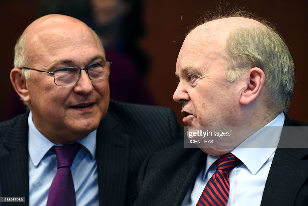 France's Minister of Finance and Public Accounts Michel Sapin (L) talks with Irish Finance Minister Michael Noonan (R) during a Eurogroup meeting at the European Union headquarters in Brussels on May 24, 2016. Eurozone finance ministers said they hoped to unlock vital bailout cash for Greece on May 24, but warned of tough talks on debt relief that the IMF has demanded as the price for staying with the programme. / AFP / JOHN