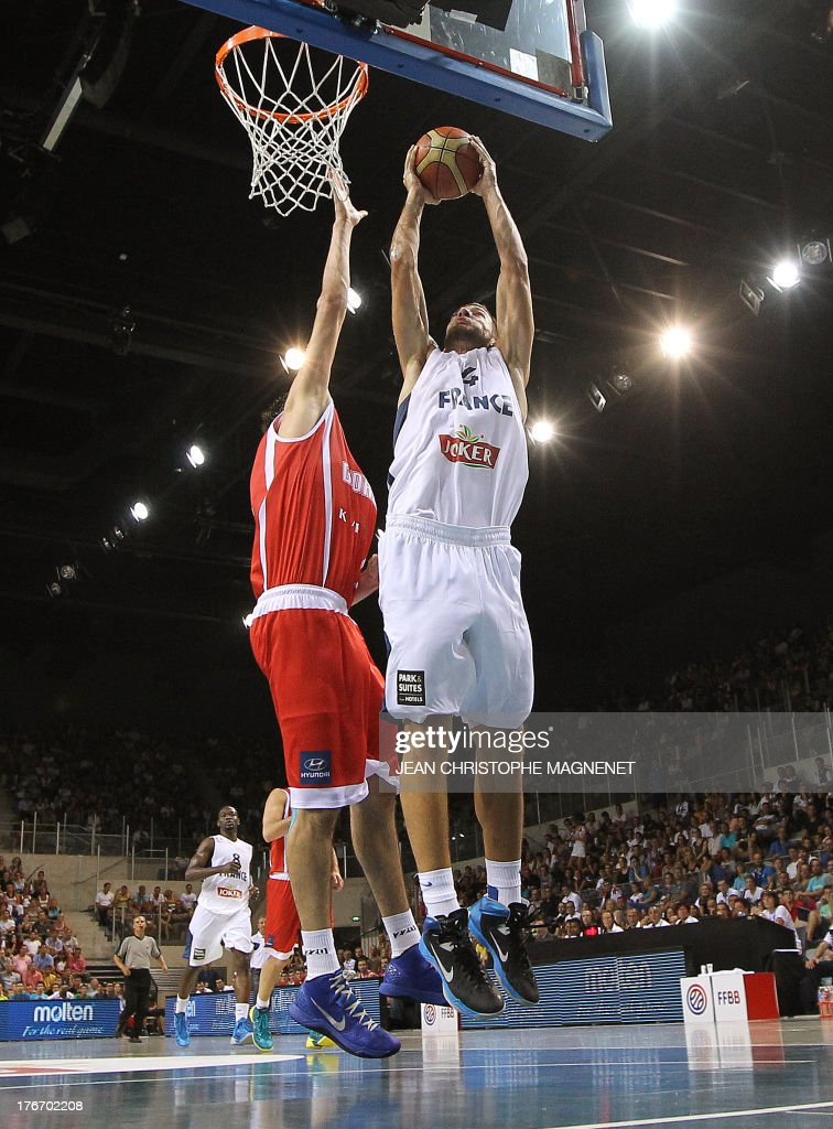 France's national basketball team player Joffrey Lauvergne (R) vies with Georgia's national basketball team player Giorgi Shermadini (L), during the friendly basketball match France vs Georgia, on August 17, 2013, in Antibes, southeastern France, as part of the preparation for the 2013 EuroBasket in Slovenia.