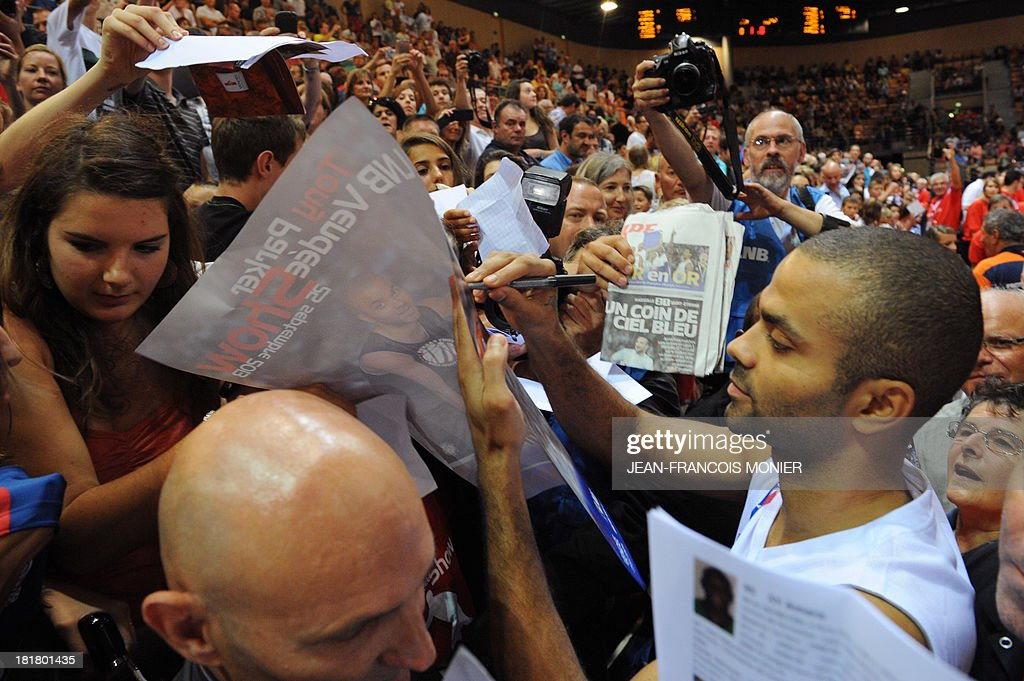 France's national basketball team point guard Tony Parker (R) signs autographs after the exibition match Tony Parker Team vs Lyon-Villeurbanne on September 25, 2013 at the Vendespace in Mouilleron-le-Captif, Western France. AFP PHOTO / JEAN-FRANCOIS MONIER