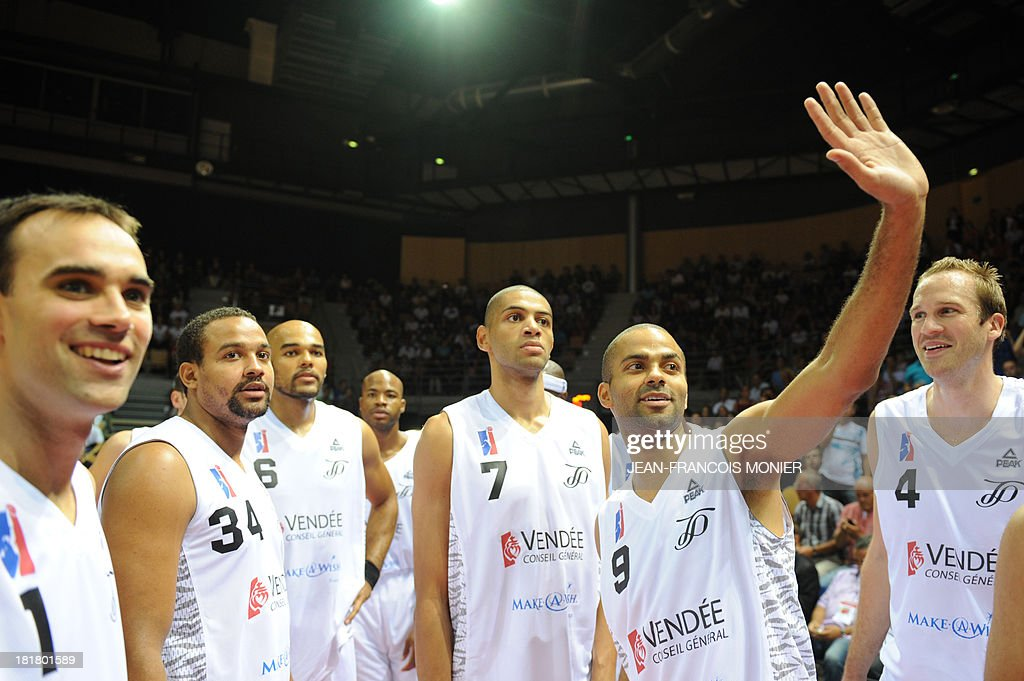 France's national basketball team point guard Tony Parker (2nd R) waves before the the exibition match Tony Parker Team vs Lyon-Villeurbanne on September 25, 2013 at the Vendespace in Mouilleron-le-Captif, Western France.